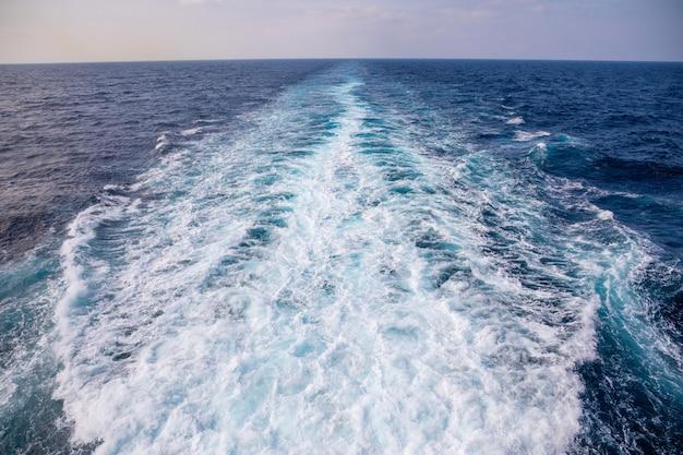 Impression de sentier sur la surface de l'eau derrière le bateau de croisière