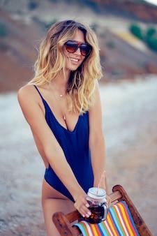 Impressionnant beauté blonde femme à lunettes de soleil, maillot de bain relaxant sur la plage et boissons cocktail. concept de vacances d'été