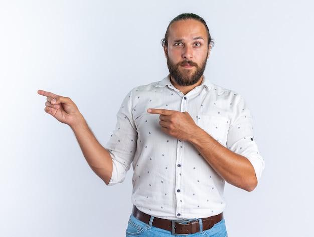 Impressionné adulte bel homme portant des lunettes regardant la caméra pointant sur le côté isolé sur mur blanc