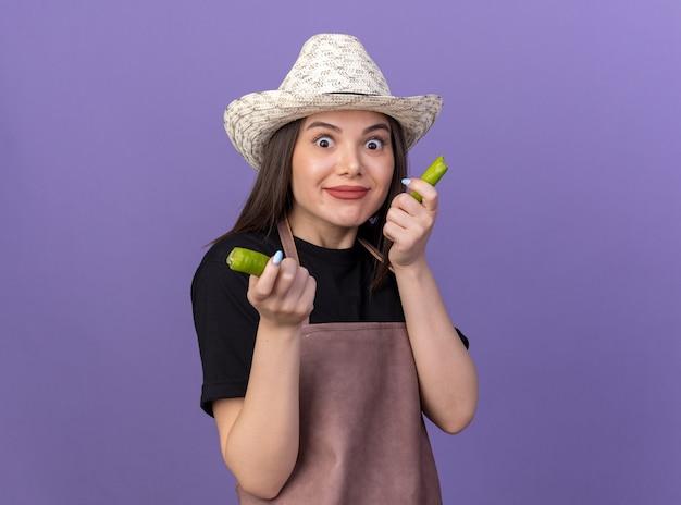 Impressionné assez caucasien femme jardinier portant chapeau de jardinage tenant des parties de piment cassé sur violet