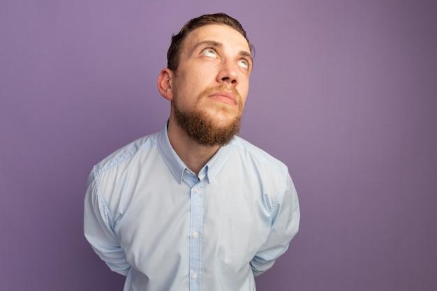 Impressionné bel homme blond lève les yeux isolé sur mur violet
