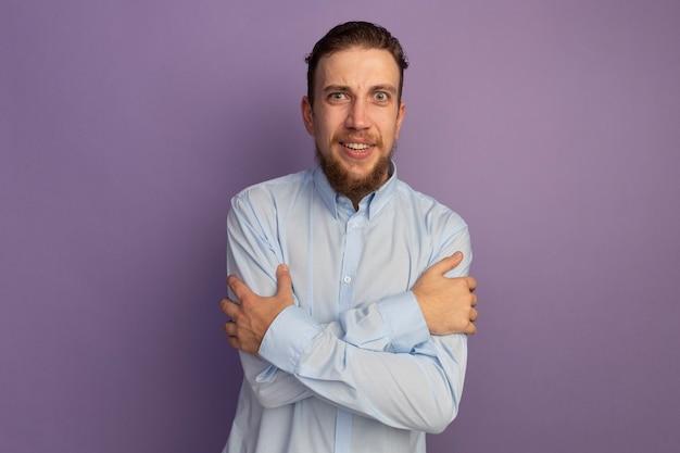 Impressionné bel homme blond tient les bras et regarde à l'avant isolé sur mur violet