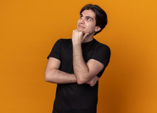 Impressionné à côté jeune beau mec portant un t-shirt noir mettant le poing sous le menton isolé sur un mur orange