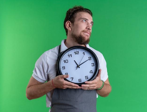 Impressionné à côté d'un jeune coiffeur masculin en uniforme tenant une horloge murale isolée sur un mur vert