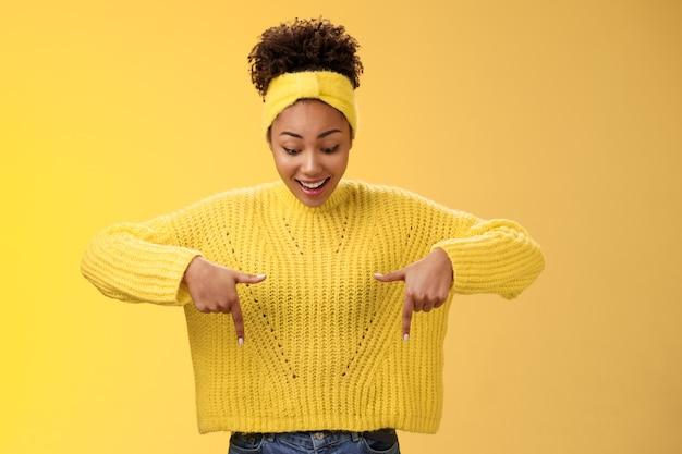 Impressionné, enthousiaste, souriant, fasciné, femme afro-américaine dans un bandeau de chandail, pointant vers le...