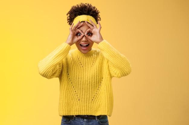 Impressionné excité charmante étudiante millénaire afro-américaine coiffure afro frisée élargir les yeux laisser tomber la mâchoire amusée montrer des lunettes de doigt regarder à travers des remises impressionnantes étonnées et ravies.