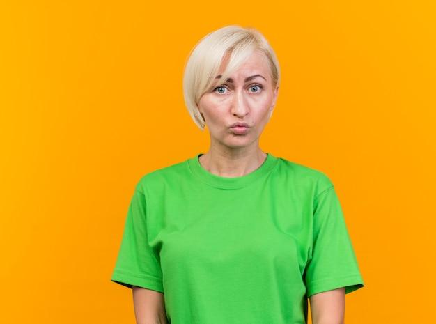 Impressionné femme blonde d'âge moyen à l'avant isolé sur mur jaune