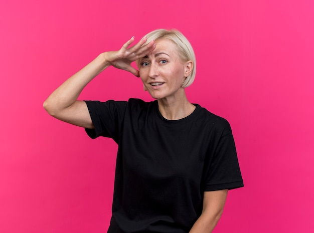 Impressionné femme blonde d'âge moyen en gardant la main sur le front à la distance à l'avant isolé sur mur rose
