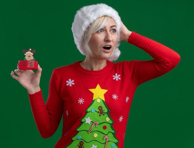 Impressionné femme blonde d'âge moyen portant chapeau de noël et chandail tenant jouet de renne de noël avec date à côté en gardant la main sur la tête isolé sur fond vert