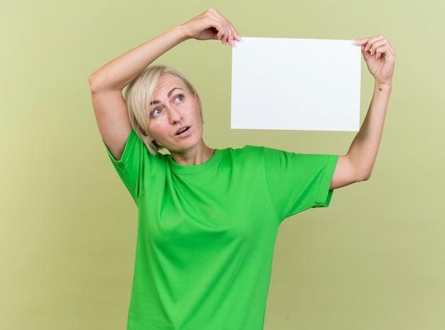 Impressionné femme blonde d'âge moyen tenant du papier blanc près de la tête en le regardant isolé sur mur vert olive