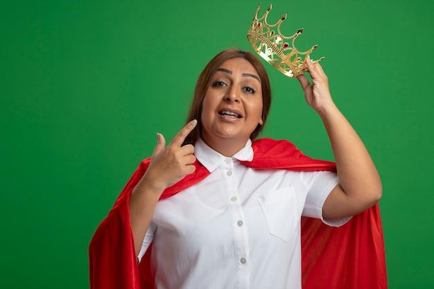 Impressionné femme de super-héros d'âge moyen mettant la couronne sur la tête isolé sur fond vert