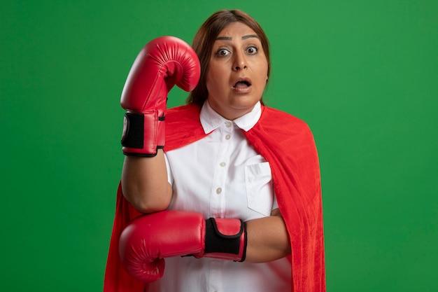 Impressionné femme de super-héros d'âge moyen portant des gants de boxe mettant la main sur la tête isolé sur vert