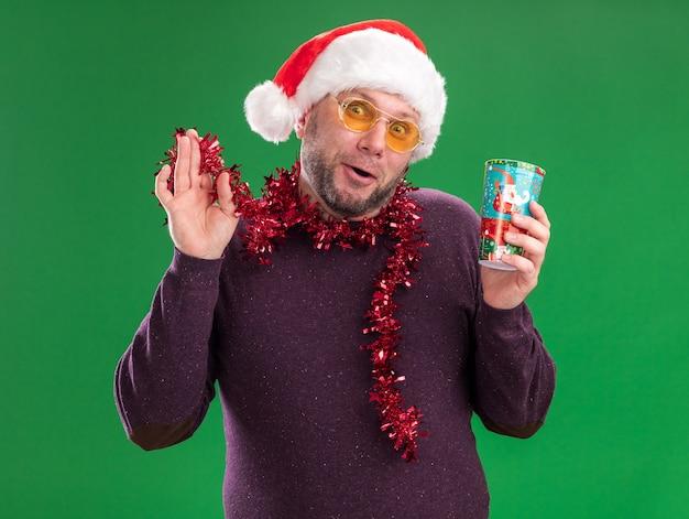Impressionné homme d'âge moyen portant bonnet de noel et guirlande de guirlandes autour du cou avec des lunettes tenant une tasse de noël en plastique saisissant guirlande de guirlandes regardant la caméra isolée sur fond vert