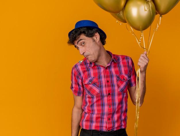 Impressionné homme d'âge moyen portant chapeau de fête tenant des ballons à l'avant avec ventilateur de fête dans la bouche isolé sur mur orange