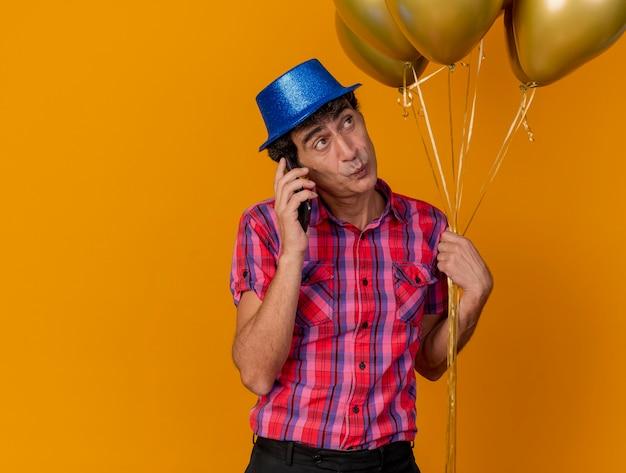 Impressionné homme d'âge moyen portant chapeau de fête tenant des ballons parler au téléphone à côté isolé sur mur orange