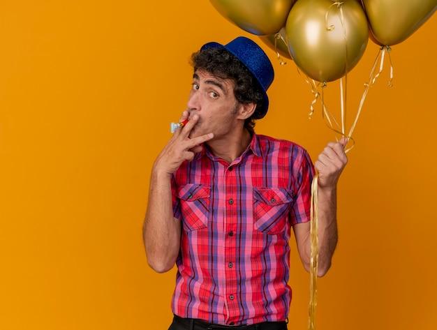 Impressionné homme de fête d'âge moyen portant chapeau de fête tenant des ballons à l'avant faire semblant de fumer à l'aide de souffleur de fête comme cigarette isolée sur mur orange