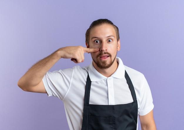 Impressionné jeune beau coiffeur en uniforme mettant le doigt sur son visage en pointant sur son nez isolé sur violet