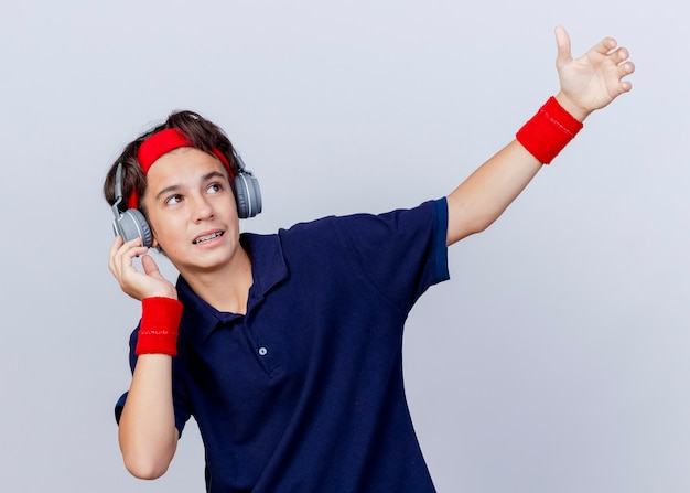 Impressionné jeune beau garçon sportif portant un bandeau et des bracelets et des écouteurs avec des appareils dentaires touchant les écouteurs en regardant sur le côté et en étirant la main isolé sur fond blanc