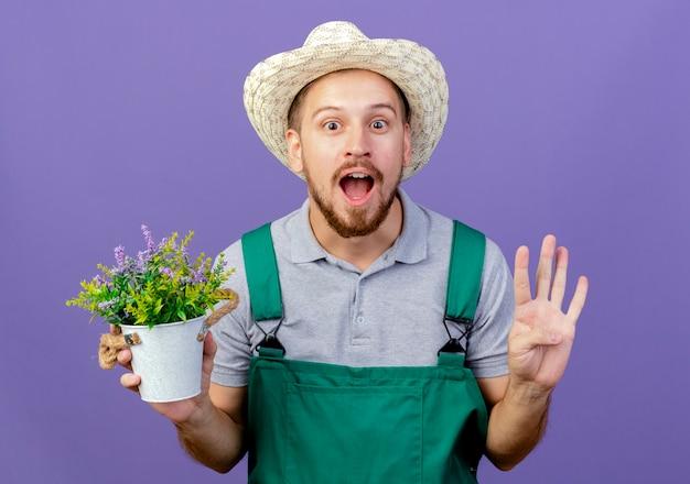 Impressionné jeune beau jardinier slave en uniforme et hat holding pot de fleurs montrant la main vide isolé sur mur violet