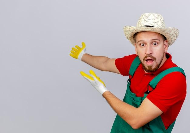 Impressionné jeune beau jardinier slave en uniforme portant des gants de jardinage et un chapeau à la recherche de pointage avec les mains derrière isolé