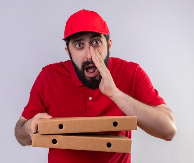 Impressionné jeune beau livreur de race blanche portant l'uniforme rouge et une casquette tenant des boîtes à pizza et chuchotant isolé sur blanc