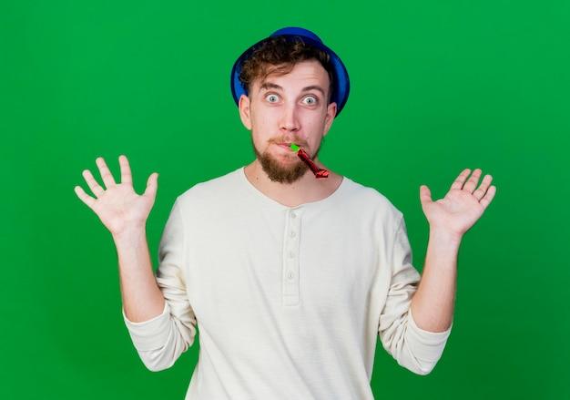 Impressionné jeune beau mec du parti slave portant chapeau de fête tenant le ventilateur de fête dans la bouche à l'avant montrant les mains vides isolés sur le mur vert
