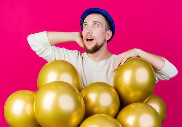 Impressionné jeune beau mec de fête slave portant chapeau de fête debout derrière des ballons en gardant la main derrière le cou en mettant un autre sur ballon en levant isolé sur fond cramoisi