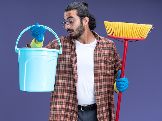 Impressionné jeune beau mec de nettoyage portant un t-shirt et des gants tenant une vadrouille et regardant un seau dans sa main isolé sur un mur bleu