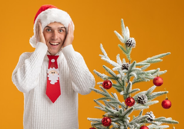Impressionné jeune beau mec portant chapeau de noël et cravate de père noël debout près de l'arbre de noël décoré en gardant les mains sur la tête en regardant la caméra isolée sur fond orange