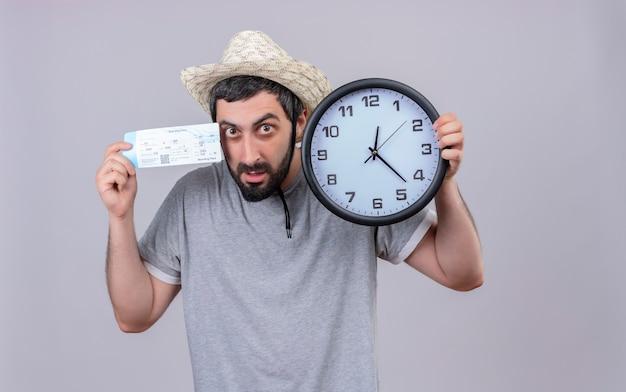Impressionné jeune beau voyageur caucasien homme portant un chapeau tenant horloge et billet d'avion isolé sur blanc avec espace copie