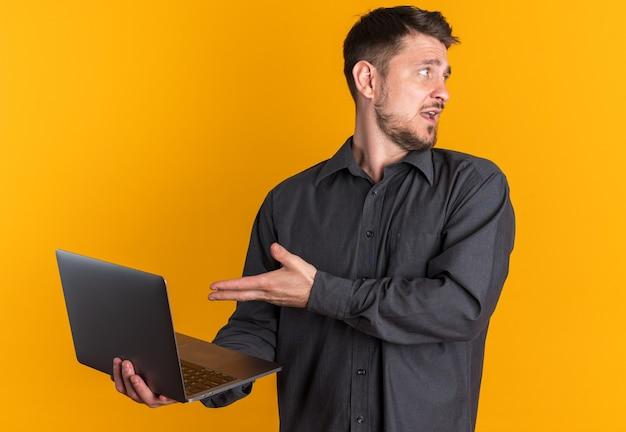 Impressionné jeune bel homme blond debout dans la vue de profil tenant et pointant sur un ordinateur portable regardant de côté
