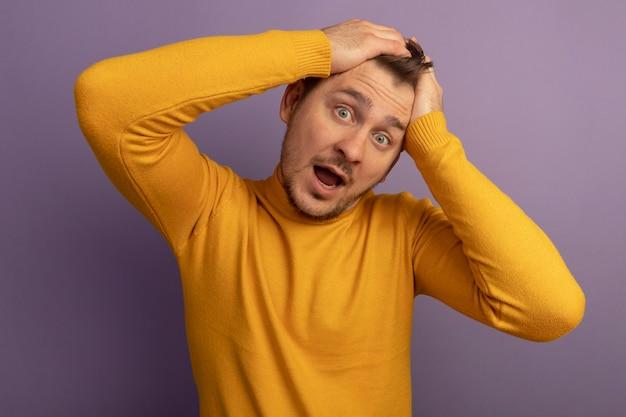 Impressionné jeune bel homme blond gardant les mains sur la tête regardant devant isolé sur mur violet
