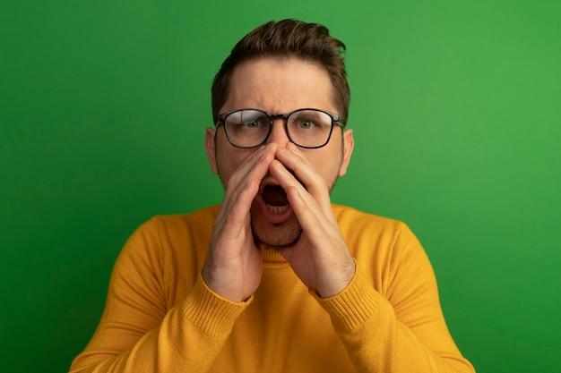 Impressionné jeune bel homme blond portant des lunettes à garder les mains autour de la bouche appelant quelqu'un isolé sur mur vert