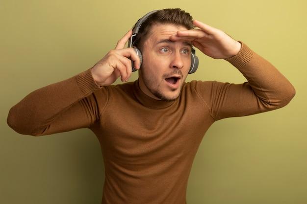 Impressionné jeune bel homme blond portant et saisissant des écouteurs mettant la main sur le front regardant de côté à distance isolé sur un mur vert olive