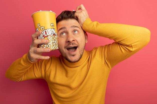 Impressionné jeune bel homme blond tenant un seau de pop-corn et un morceau de pop-corn touchant la tête avec un seau de pop-corn et la main levant isolé sur un mur rose