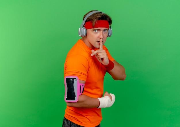 Impressionné jeune bel homme sportif portant un bandeau et des bracelets et des écouteurs et un brassard de téléphone avec un poignet enveloppé d'un bandage debout dans la vue de profil faisant des gestes de silence