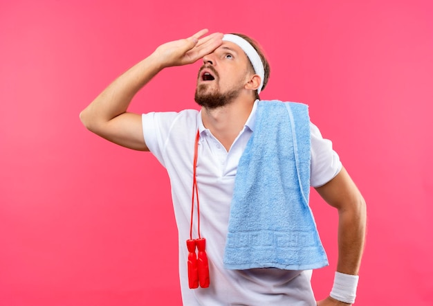 Impressionné jeune bel homme sportif portant un bandeau et des bracelets mettant la main sur le front et levant les yeux avec une serviette et une corde à sauter sur les épaules isolées sur un mur rose