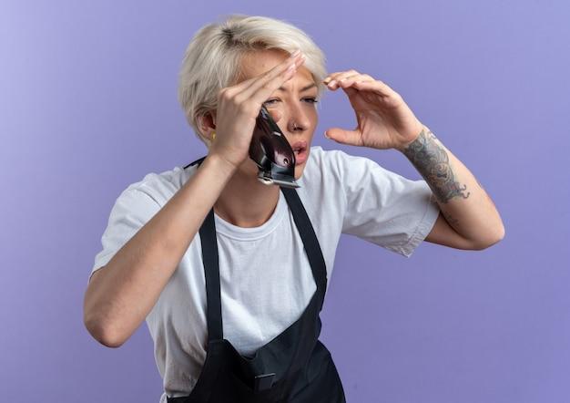 Impressionné jeune belle femme barbier en uniforme tenant une tondeuse à cheveux à la distance avec les mains isolées sur le mur bleu