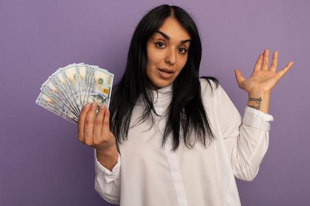 Impressionné jeune belle fille portant un t-shirt blanc tenant la main de diffusion de trésorerie isolé sur violet