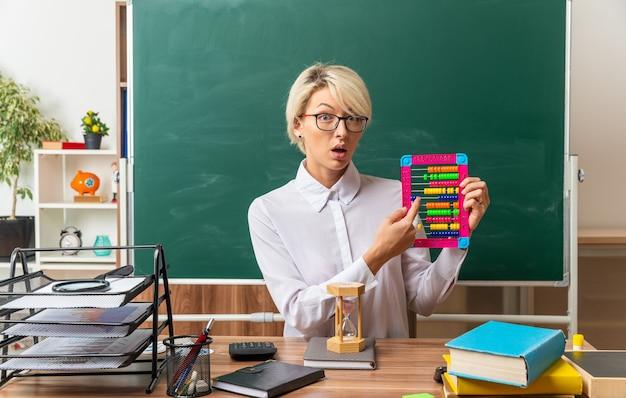 Impressionné jeune blonde enseignante portant des lunettes assis au bureau avec des fournitures scolaires en classe montrant abacus pointant sur elle