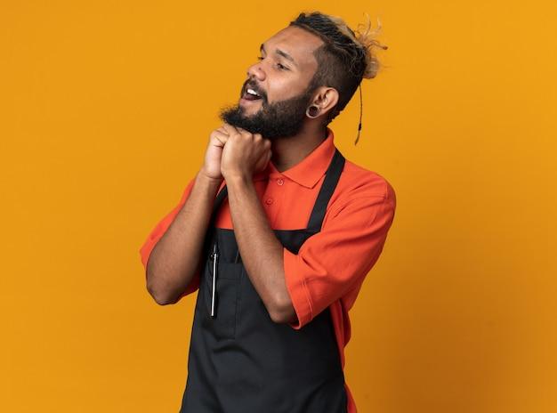 Impressionné jeune coiffeur afro-américain en uniforme gardant les mains sous le menton en regardant le côté