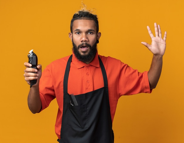 Impressionné jeune coiffeur afro-américain en uniforme tenant une tondeuse à cheveux montrant cinq avec la main