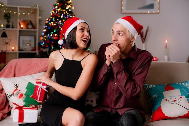 Impressionné jeune couple à la maison à l'époque de noël portant bonnet de noel assis sur un canapé dans le salon recevant des cadeaux