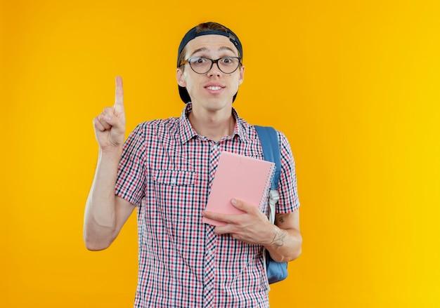 Impressionné jeune étudiant garçon portant sac à dos et lunettes et casquette tenant un cahier et des points vers le haut