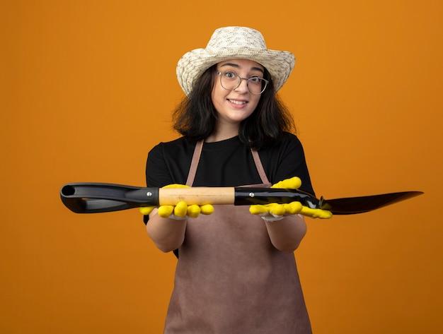 Impressionné jeune femme brune jardinière dans des lunettes optiques et en uniforme portant chapeau de jardinage et des gants détient spade isolé sur mur orange