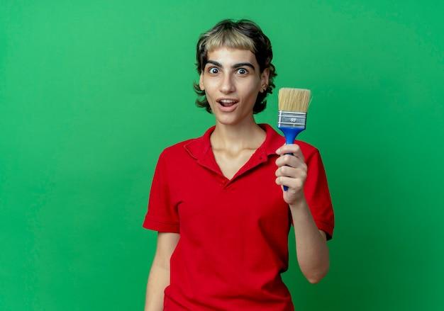 Impressionné jeune femme avec coupe de cheveux de lutin tenant un pinceau