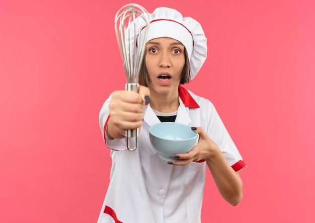 Impressionné jeune femme cuisinier en uniforme de chef s'étendant fouet et tenant bol isolé sur rose avec copie espace