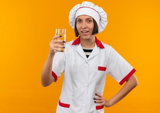 Impressionné jeune femme cuisinier en uniforme de chef tenant un verre d'eau mettant la main sur la taille isolé sur orange avec copie espace
