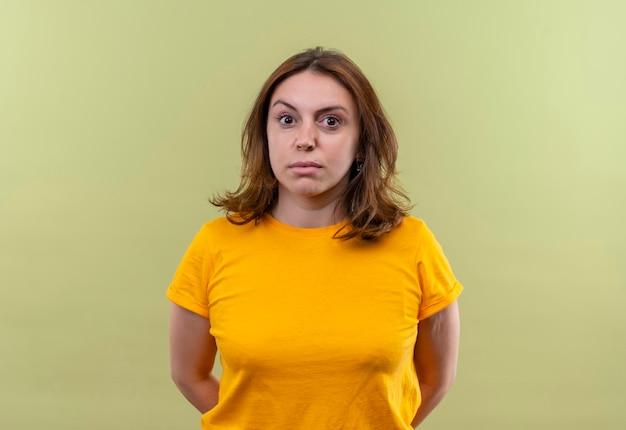 Impressionné jeune femme décontractée avec les mains derrière le dos sur un espace vert isolé avec copie espace