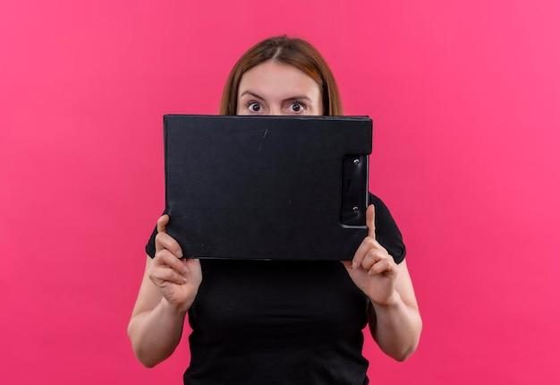 Impressionné jeune femme décontractée tenant le presse-papiers et se cachant derrière elle sur l'espace rose isolé